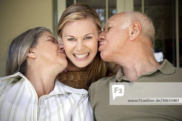 Porträt einer lächelnden Frau mit küssenden Eltern