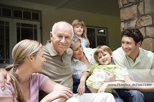 Gruppenbild von drei Generationen Familie auf der Terrasse sitzend
