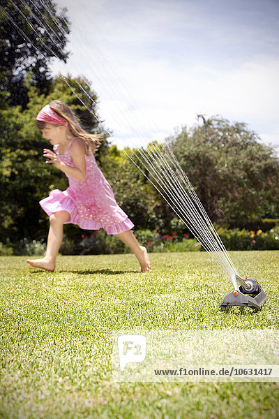 Kleines Mädchen spielt mit Rasensprenger im Garten Kleines Mädchen spielt mit Rasensprenger im Garten