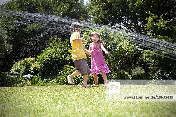 Zwei kleine Kinder beim Spielen mit Rasensprenger im Garten