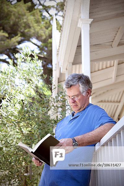 Mann  der sich gegen die Balustrade lehnt und ein Buch liest. Mann, der sich gegen die Balustrade lehnt und ein Buch liest.