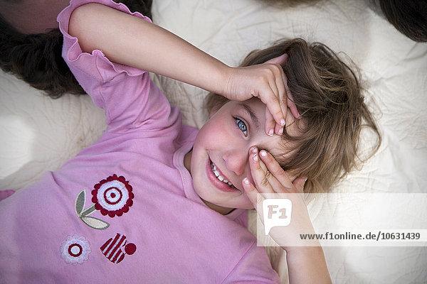 Kleines Mädchen auf Decke liegend  ein Auge mit der Hand bedeckend Kleines Mädchen auf Decke liegend, ein Auge mit der Hand bedeckend