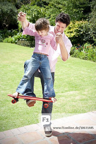 Mann spielt mit seiner kleinen Tochter im Garten
