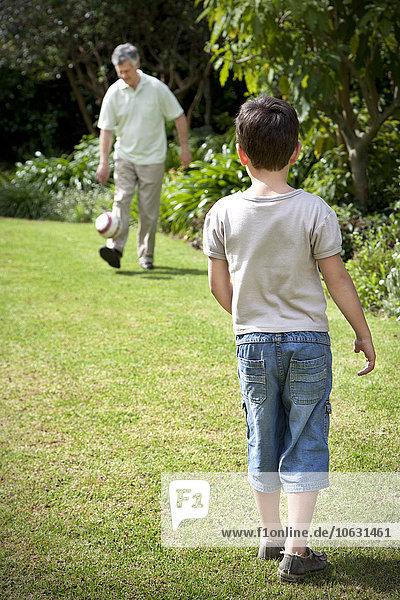 Kleiner Junge spielt Fußball mit seinem Großvater