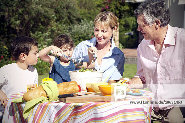 Kleiner Junge und Mädchen mit den Großeltern am Esstisch im Garten Kleiner Junge und Mädchen mit den Großeltern am Esstisch im Garten
