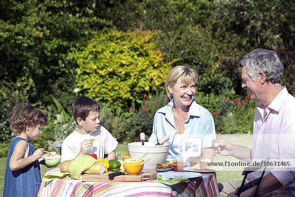 Kleiner Junge und Mädchen mit den Großeltern am Esstisch im Garten