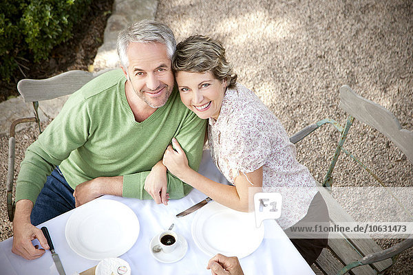 Porträt eines lächelnden Paares am gedeckten Tisch im Garten mit Blick auf die Kamera Porträt eines lächelnden Paares am gedeckten Tisch im Garten mit Blick auf die Kamera