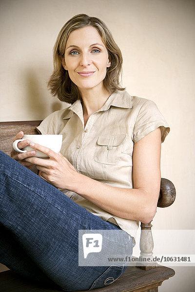 Porträt einer entspannten jungen Frau auf einer Holzbank mit einer Tasse Cappuccino