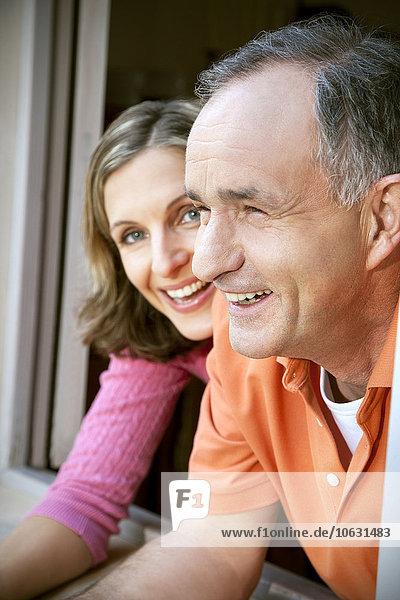 Mann und junge Frau lehnen sich aus dem Fenster.