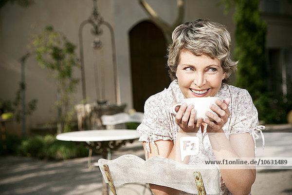 Spanien  Mallorca  Porträt der lächelnden reifen Frau im Garten mit Tasse Cappuccino Spanien, Mallorca, Porträt der lächelnden reifen Frau im Garten mit Tasse Cappuccino