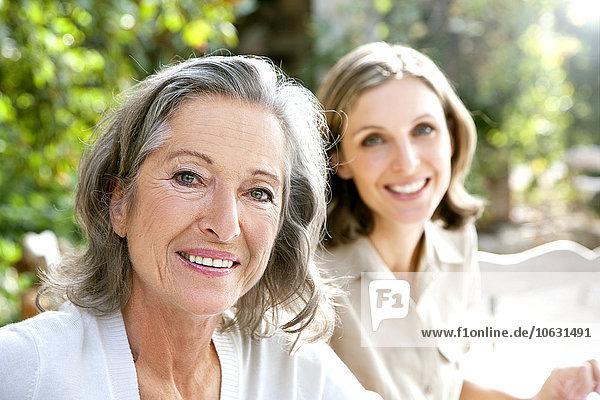 Porträt der lächelnden reifen Frau und der jungen Frau im Hintergrund
