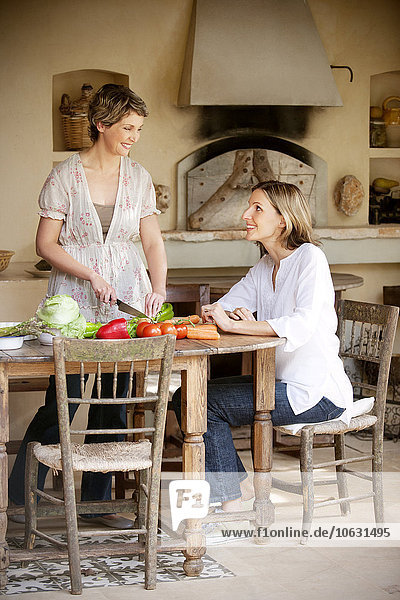 Zwei Freundinnen bereiten Gemüse in der Küche zu.