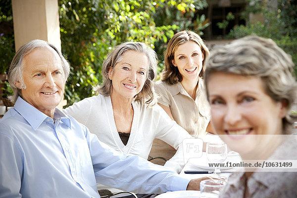 Vier lächelnde Freunde sitzen am gedeckten Tisch im Garten.