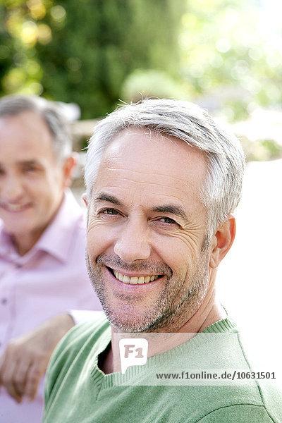 Porträt eines lächelnden Mannes mit grauen Haaren und Stoppeln Porträt eines lächelnden Mannes mit grauen Haaren und Stoppeln