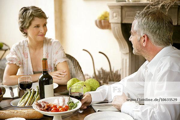 Ein Paar sitzt am gedeckten Tisch und schaut sich an. Ein Paar sitzt am gedeckten Tisch und schaut sich an.