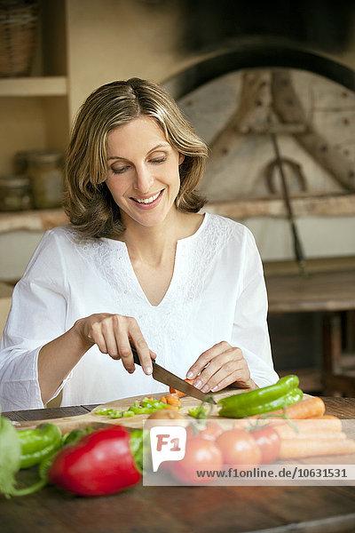 Porträt einer lächelnden Frau beim Gemüsehacken Porträt einer lächelnden Frau beim Gemüsehacken