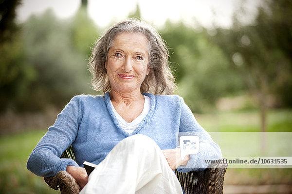 Porträt einer lächelnden Frau mit Buch im Korbsessel im Garten sitzend