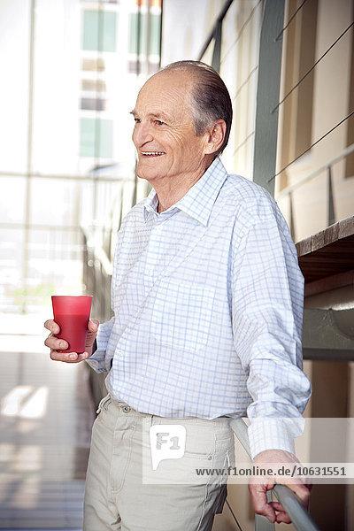 Lachender Senioren  der sich auf das Geländer stützt. Lachender Senioren, der sich auf das Geländer stützt.