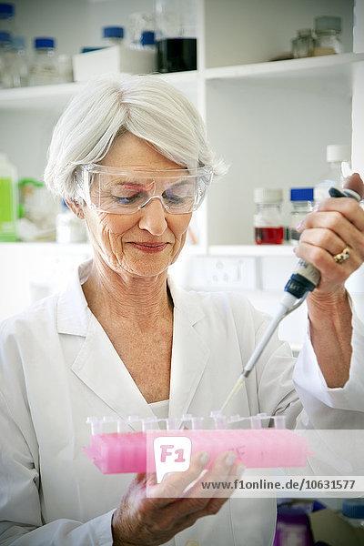 Professorin beim Füllen von Probengläsern im Laoratorium Professorin beim Füllen von Probengläsern im Laoratorium