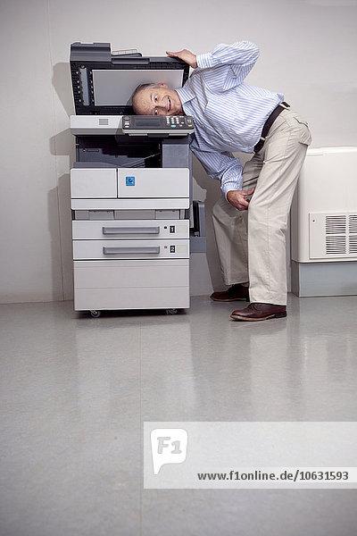 Senior Mann setzt Kopf in Kopiergerät ein Senior Mann setzt Kopf in Kopiergerät ein