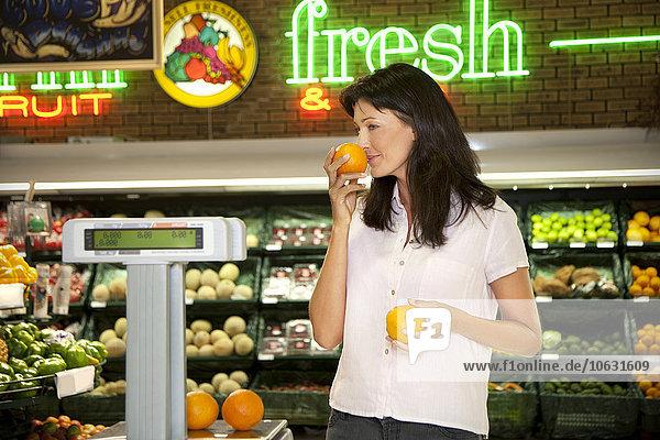 Kunde riecht Orange im Supermarkt