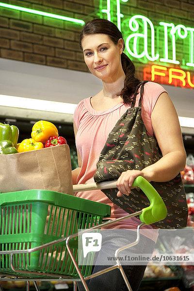 Porträt eines lächelnden Kunden mit Einkaufswagen beim Gemüsekauf im Supermarkt Porträt eines lächelnden Kunden mit Einkaufswagen beim Gemüsekauf im Supermarkt
