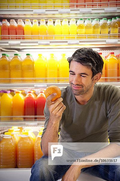 Porträt eines lächelnden Mannes vor dem Kühlschrank mit Reihen von Saftflaschen in einem Supermarkt mit einer Orange. Porträt eines lächelnden Mannes vor dem Kühlschrank mit Reihen von Saftflaschen in einem Supermarkt mit einer Orange.