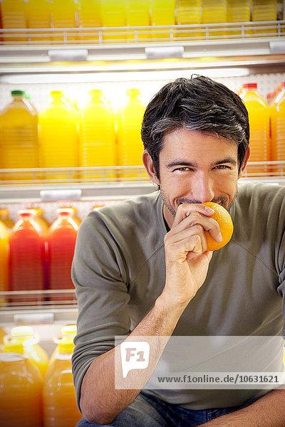 Porträt eines lächelnden Mannes vor dem Kühlschrank mit Reihen von Saftflaschen in einem Supermarkt mit Orangenduft. Porträt eines lächelnden Mannes vor dem Kühlschrank mit Reihen von Saftflaschen in einem Supermarkt mit Orangenduft.
