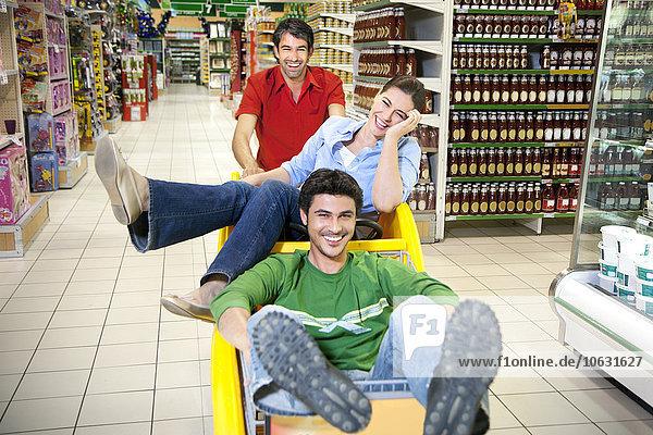 Drei Freunde beim gemeinsamen Vergnügen im Supermarkt