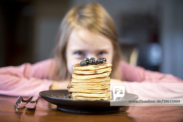 Teller mit Pfannkuchenstapel mit kleinem Mädchen im Hintergrund