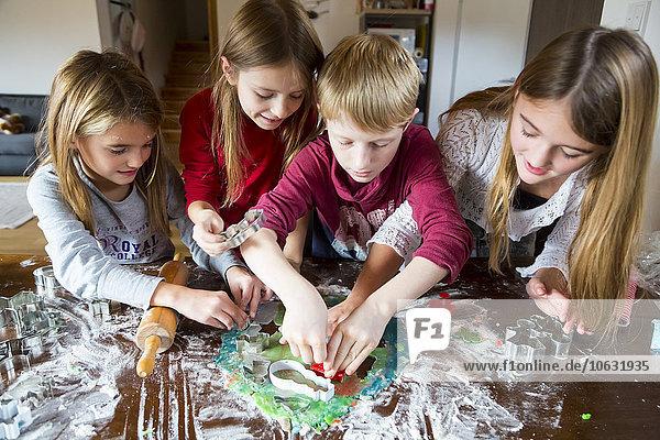 Vier Kinder schneiden zu Hause Weihnachtsplätzchen aus.