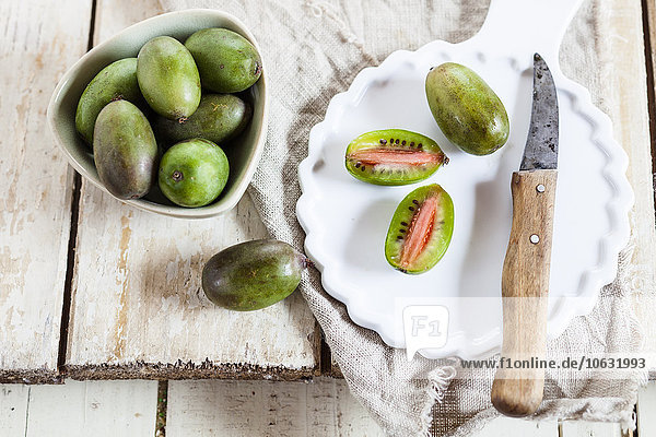 Geschnittene und ganze Mini-Kiwi auf dem Teller