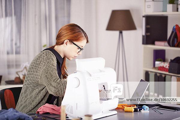 Porträt einer jungen Frau mit Nähmaschine zu Hause