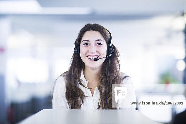 Porträt einer lächelnden jungen Frau mit Headset im Büro
