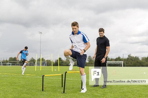 Trainer-Training mit Fußballspielern auf dem Sportplatz