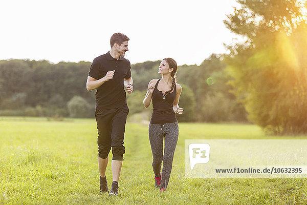 Mann und Frau beim Joggen auf dem Feld