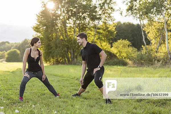Mann und Frau beim Stretching im Feld