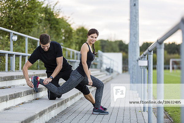 Mann assistierende Frau beim Training auf dem Sportplatz