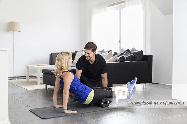 Coach bei Übungen mit der Frau zu Hause