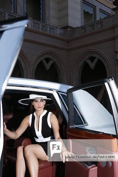 VAE  Abu Dhabi  Porträt einer modischen Frau  die auf dem Rücksitz eines Autos sitzt.