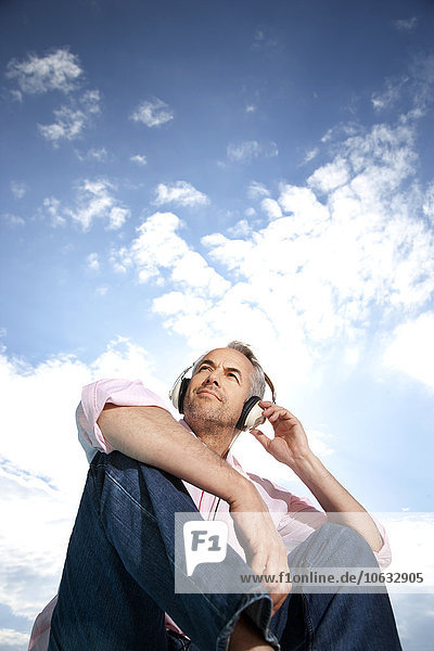 Porträt eines Mannes  der Musik mit Kopfhörern vor bewölktem Himmel hört. Porträt eines Mannes, der Musik mit Kopfhörern vor bewölktem Himmel hört.
