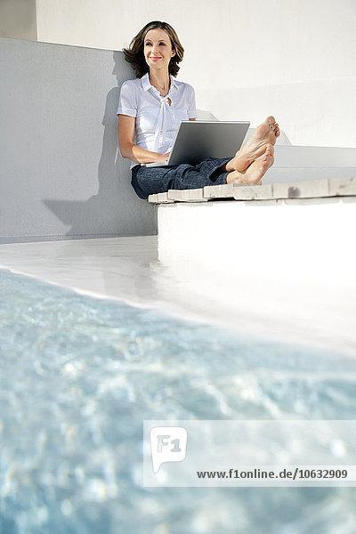 Spanien  Mallorca  Porträt einer lächelnden Frau mit Laptop neben dem Swimmingpool Spanien, Mallorca, Porträt einer lächelnden Frau mit Laptop neben dem Swimmingpool