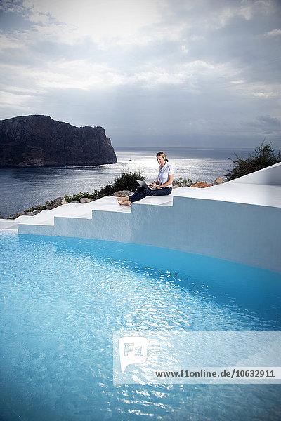Spanien  Mallorca  Frau mit Laptop auf einer Treppe neben einem Swimmingpool mit Meer im Hintergrund Spanien, Mallorca, Frau mit Laptop auf einer Treppe neben einem Swimmingpool mit Meer im Hintergrund
