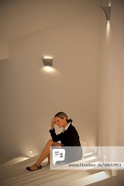 Überlastete Geschäftsfrau auf der Treppe sitzend Überlastete Geschäftsfrau auf der Treppe sitzend