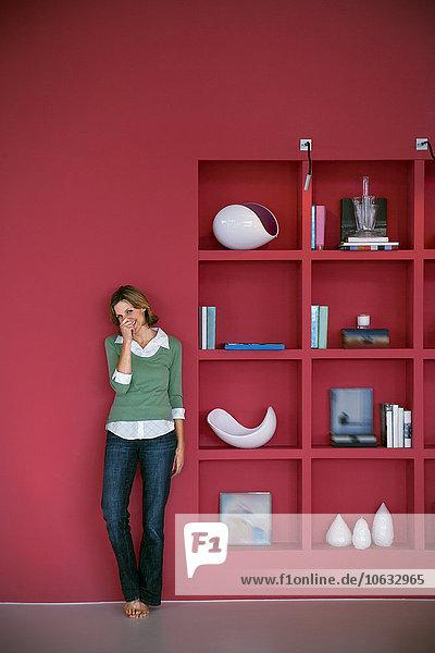 Lachende Frau lehnt sich an die rote Wand. Lachende Frau lehnt sich an die rote Wand.
