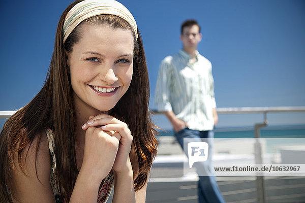 Porträt einer lächelnden jungen Frau mit Mann im Hintergrund Porträt einer lächelnden jungen Frau mit Mann im Hintergrund