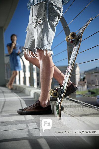 Junger Mann mit Skateboard auf dem Balkon und Frau im Hintergrund Junger Mann mit Skateboard auf dem Balkon und Frau im Hintergrund