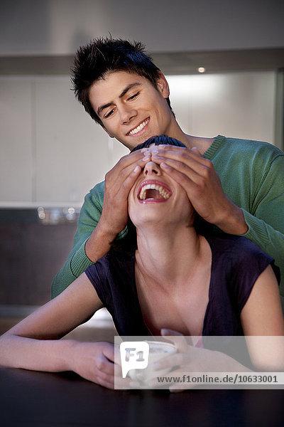 Lächelnder junger Mann  der die Augen der Freundin bedeckt. Lächelnder junger Mann, der die Augen der Freundin bedeckt.