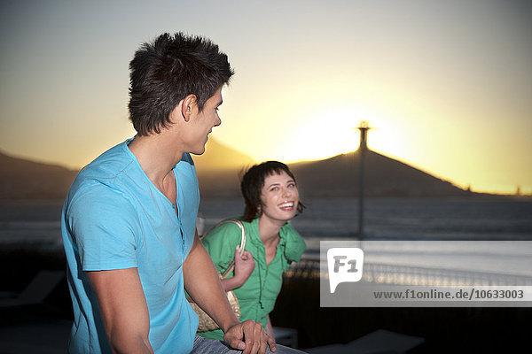 Fröhlicher junger Coupke an der Küste bei Sonnenuntergang Fröhlicher junger Coupke an der Küste bei Sonnenuntergang