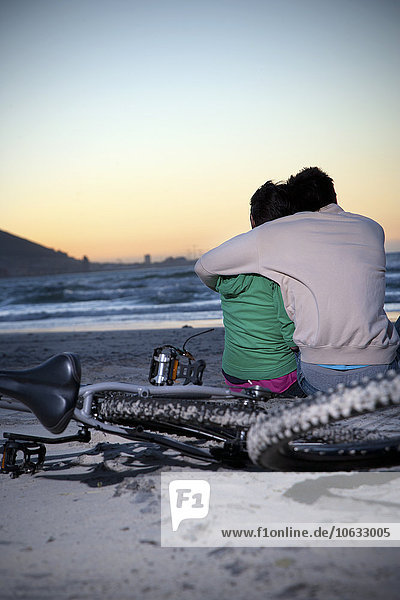 Junges Paar  das sich bei Sonnenuntergang am Strand umarmt Junges Paar, das sich bei Sonnenuntergang am Strand umarmt